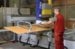 The vacuum tube lifter JumboErgo 110 being used for ergonomic and precise loading of a CNC machine tool.